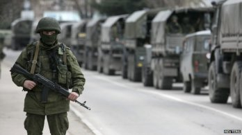 """Unmarked trucks with Putin's so-called """"little green men"""" - heavily-armed Russian cadres military troops hiding their identities and without insignia during the invasion into the Ukrainian peninsula of Crimea in February 2014."""