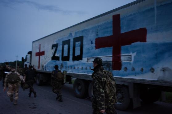 """""""Fracht 200"""" ist eine in Russland übliche Bezeichnung für gefallene Soldaten auf dem Rückweg in die Heimat. Dieses Foto zeigt einen notdürftig bemalten Lastwagen mit einer Ladung Leichen von russischen """"Freiwilligen"""", die in der Ukraine bei den Kämpfen getötet wurden. Foto: Maria Turchenkova/Echo Photo Agency"""
