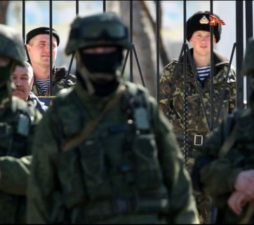 "A Ukrainian base in Crimea surrounded by the ""little green men,"" heavily armed troops wearing no ensignia to hide the fact that the troops were Russian special forces. February 2014"