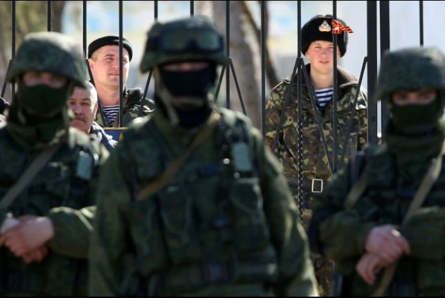 """A Ukrainian base in Crimea surrounded by the """"little green men,"""" heavily armed troops wearing no ensignia to hide the fact that the troops were Russian special forces. February 2014"""