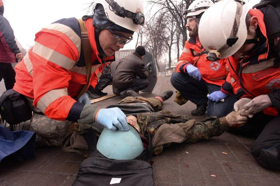 February 20, 2014. Instytutska Street, Kyiv, Ukraine. Roman (second to the right) and volunteer doctors are examining the body of Ustym Golodnyuk. Roman will be shot in a few seconds. Photograph: Mstislav Chernov.