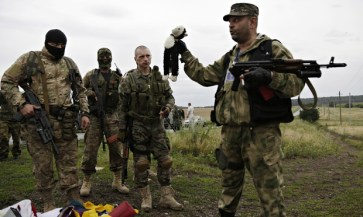 Russian mercenaries taking photographs with personal items found among the debris at the crash site of MH17 downed by a Russian BUK surface-to-air missile in Russia-occupied east Ukraine