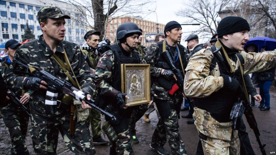 Lugansk separatists holding an Orthodox icon by the taken over SBU building, April 14th, 2014. Photo: AFP