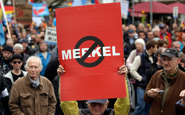 """People take part in a protest rally of the German party 'Alternative fuer Deutschland, AfD' (Alternative for Germany) in Berlin. The anti-immigration party staged a march in Berlin against the German government's migrant policies, with demonstrators chanting """"Merkel must go"""" Photo: AP"""