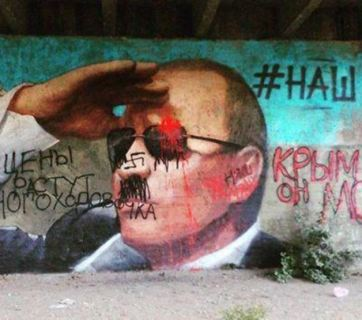 """A propagandist mural of Putin in occupied Yalta, Crimea sported a hashtag """"#НАШ"""" ( Russian for """"ours"""") to claim that Crimea is now Russian. The graffiti by Crimean residents that quickly covered it disagreed with the Kremlin statement and expressed what they think about Putin's Crimean Anschluss. May 2015 (Image: social networks)."""