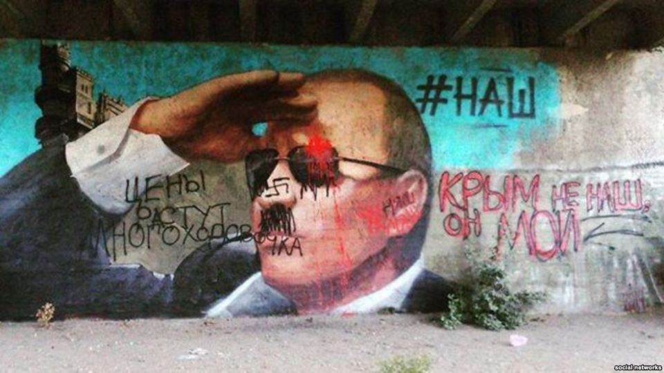 "A propagandist mural of Putin in occupied Yalta, Crimea sported a hashtag ""#НАШ"" ( Russian for ""ours"") to claim that Crimea is now Russian. The graffiti by Crimean residents that quickly covered it disagreed with the Kremlin statement and expressed what they think about Putin's Crimean Anschluss. May 2015 (Image: social networks)."