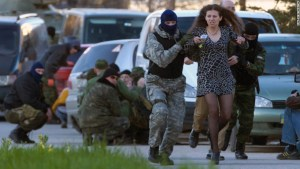 "Russian special forces and mercenaries ""evacuate"" a local resident as Russian troops assault the Ukrainian Belbek airbase, outside Sevastopol, Crimea, on Saturday, March 22, 2014. (Image: AP Photo/Ivan Sekretarev)"