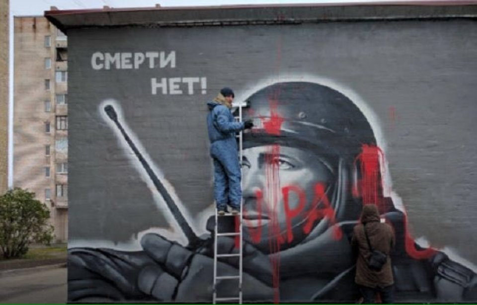 "When Putin's propaganda machine quickly started spinning to capitalize on Motorola's death by painting murals in his honor, in St.Petersburg, an unknown wrote the word ""Scum"" on one of them. (Image: social media)"