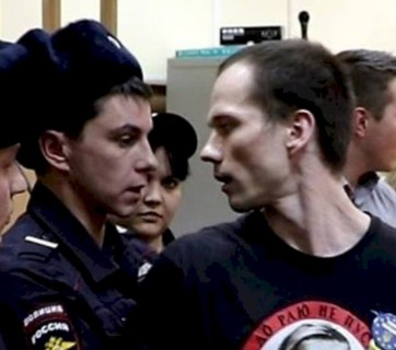 Ildar Dadin being brought into police precinct after one of his single-person protests (Image: social media)