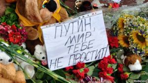 """Flowers left near the Dutch embassy in Kyiv, Ukraine for victims of Malaysia Airlines MH17. The note says in Russian: """"Putin, the world will not forgive you."""""""