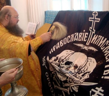 "Russian Orthodox priest blesses a flag with a sign ""The Orthodox Church or Death"" (Image: politros.com)"