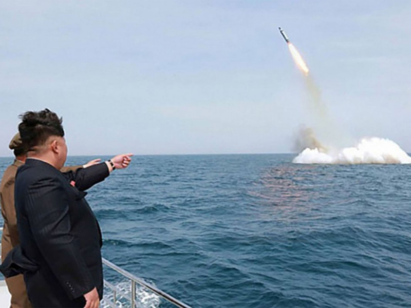 """Kim Jong Un, the """"Supreme Leader"""" of North Korea, supervises the April 22 test-launch of a missile from a submerged platform. (Image source: KCNA)"""