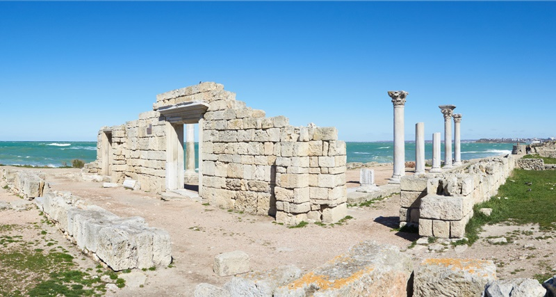 Tauric Chersonesos' ancient ruins are presently located in one of Sevastopol's suburbs. The buildings mix influences of Greek, Roman and Byzantine culture. The defensive wall was approximately 3.5 kilometres (2.2 mi) long, 3.5 to 4 metres wide and 8 to 10 metres high with towers at a height of 10 to 12 metres. The walls enclosed an area of about 30 hectares (74 acres). Buildings include a Roman amphitheatre and a Greek temple. (Image: qha.com.ua)
