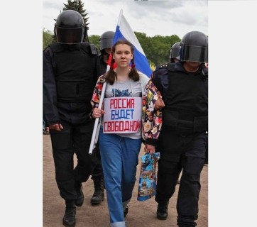 "The sign on the woman's chest says: ""Russia Will Be Free!"""