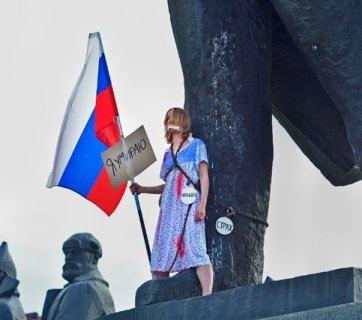 "A woman dressed as Russia in a blood-stained outfit and holding a national flag chained herself to a Lenin statue in Novosibirsk to protest deteriorating human rights and increasing poverty in Russia. The large sign attached to the flag said: ""I Am Dying."" Three smaller signs hanging off the chain said: ""Police,"" ""Fear"" and ""Censorship."" August 22, 2017 (Image: Alyona Martynova / Sib.fm)"