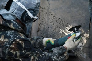 A worker in Moscow using a tool to erase the image of an earlier and similar German automatic rifle STG-44 from the recently opened monument to the creator of AK-47. (Image: social media)