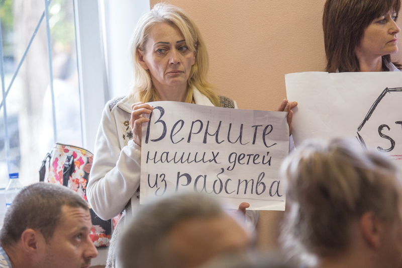"""Return our children from slavery."" Mother of an imprisoned victim of the drug trafficking scheme holds a placard during a court hearing of the criminal suspects in the case. Photo: tyzhden.ua"