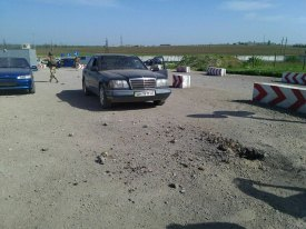 Crater of the explosion caused by a ATGM attack from the occupied territory on the Ukrainian entry-exit checkpoint at Hnutove, Mariupol area on 5 May. Fortunately, no one was hurt, but two cars were damaged. Photograph: Facebook/pressjfo.news