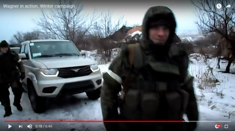 An armed man in uniform in the foreground of UAZ pickup (5m18s)