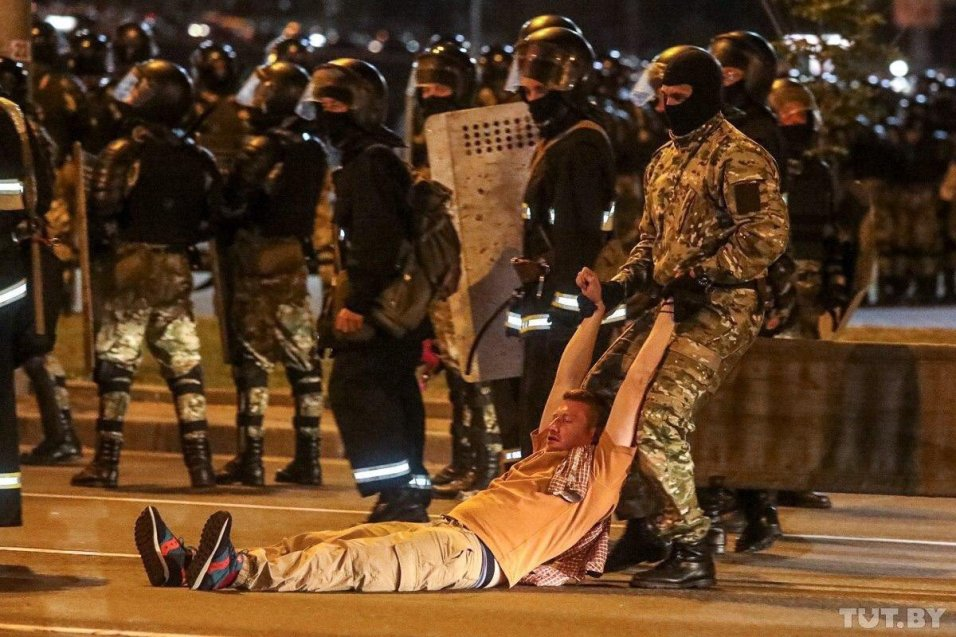 Riot police drag a protester to a paddy wagon. Photo: tut.by