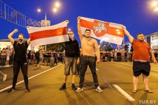 Protesters in Belarus brandish the White-Red-White and Pahonya flags. Photo: Olha Shukailo, tut.by