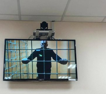 Russian opposition leader Aleksei Navalny currently imprisoned by the Putin regime is seen on a screen via a video link during a court hearing in June, 2021. (Photo: TASS)