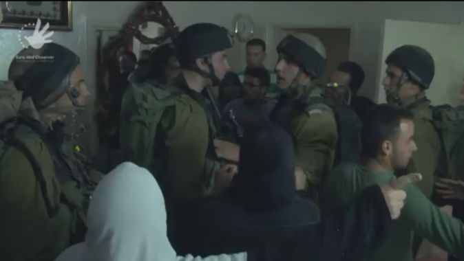 Israeli soldiers in Ayad's home as relatives and townspeople are chasing them out.
