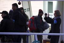 A Frontex officer (R) takes a picture as migrants board a Turkish-flagged passenger boat to be returned to Turkey, on the Greek island of Lesbos, April 4, 2016. REUTERS/Giorgos Moutafis