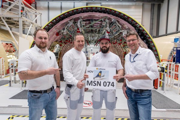 """Airbus-Mitarbeiter vor dem Rumpf der ersten A350-900 der Lufthansa mit der Fertigungsnummer """"MSN074"""" (© Airbus)"""