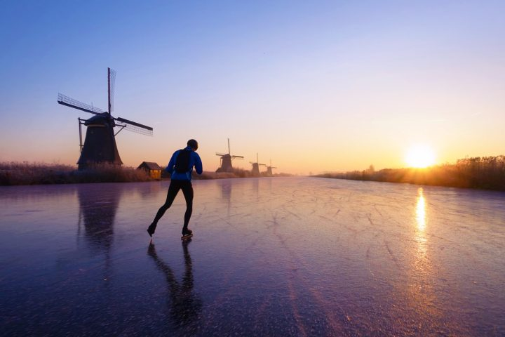 Ice skating on the canals of Kinderdijk among historical windmills