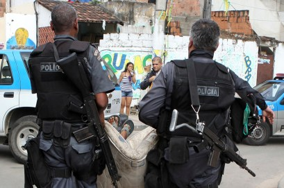 Policemen carry a suspected drug trafficker after a shootout as they conduct a raid on drug gangs at the Mandela 2 slum in Rio de Janeiro