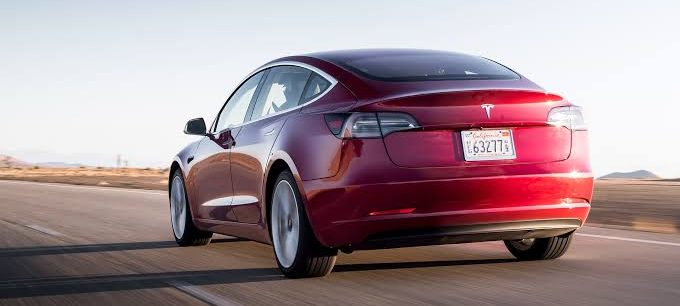 red model 3 driving away