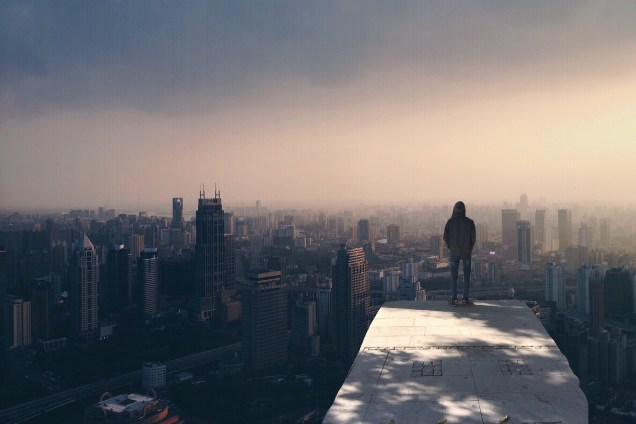 Man on a ledge over looking city