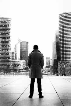 man standing looking at a city black and white
