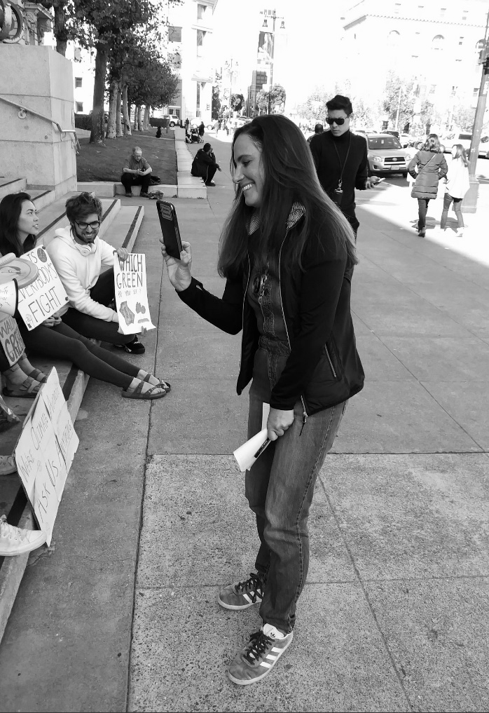 A photo of Rachel Sarah at a climate strike in 2019, interviewing youth climate activists.