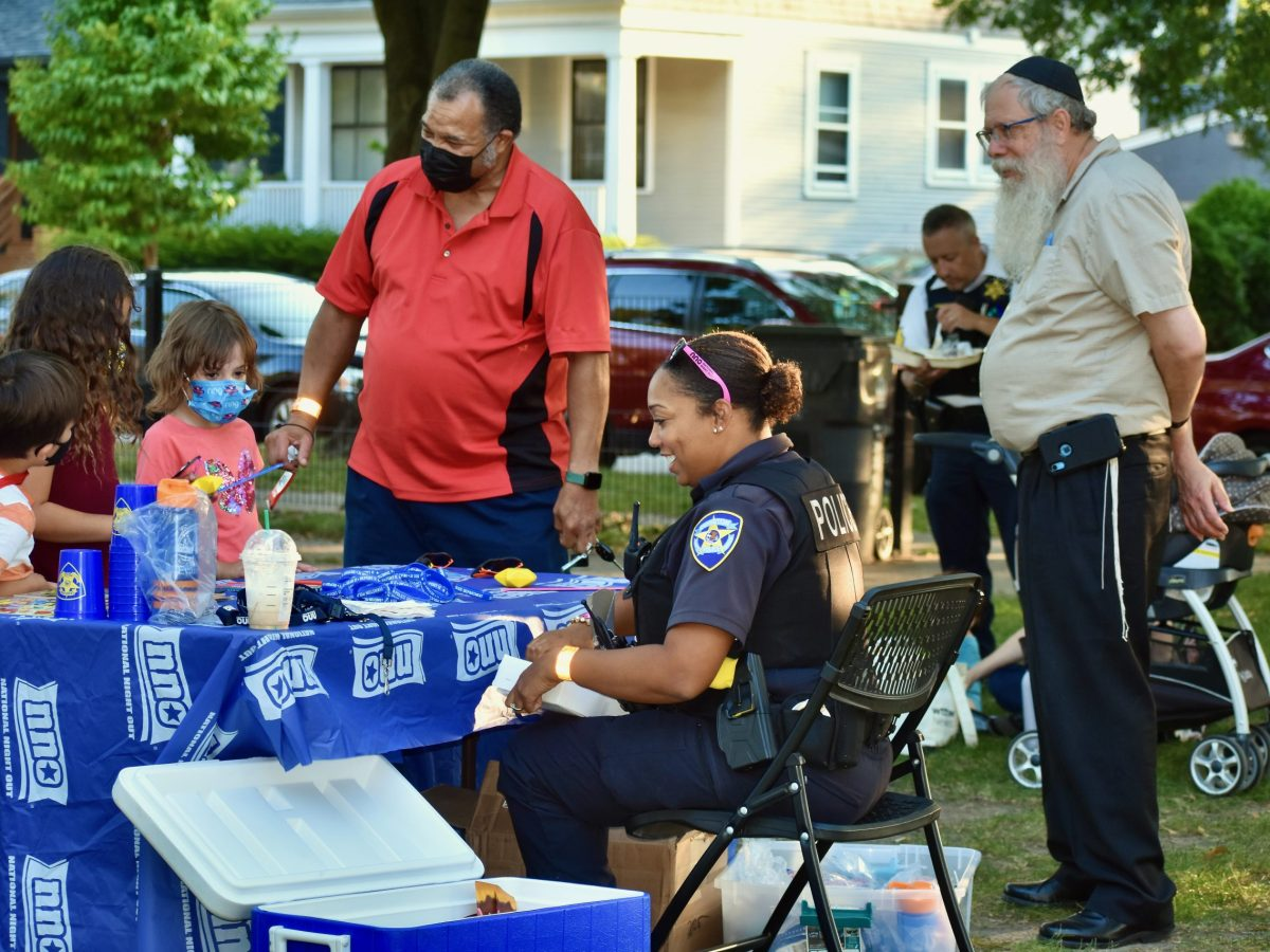 Officer Daley offered giveaways for children at Penny Park. Rodney Greene, left, and Rabbi Dov Klein were on hand to help out.