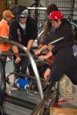 High school students mounting an electric motor on the rear swing arm of the Switch electric car