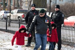 A veteran and his young children walk past members of the Winnipeg Police Service before the service begins.