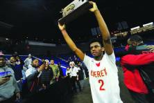 Ghared Boyce hoists the Div. 1 North Sectional trophy following the Crimson Tide's 68-56 victory over Lawrence. The win gave Everett its first sectional crown since 1994.
