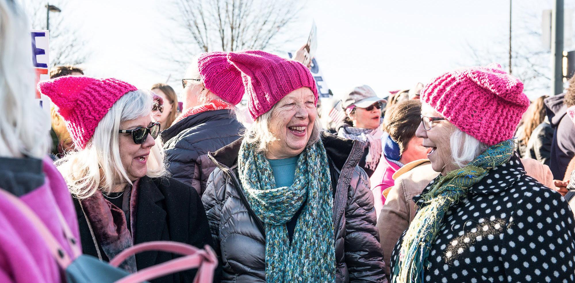 Women in pink hats chat at march