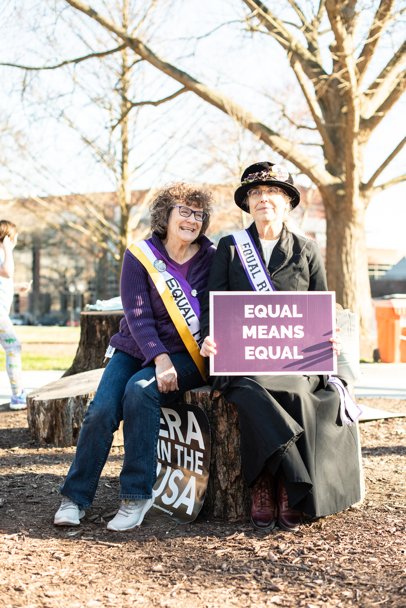 Woman in Suffragate costume holds sign