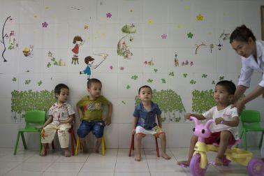 Children in Vietnam watching as one child rides a bike