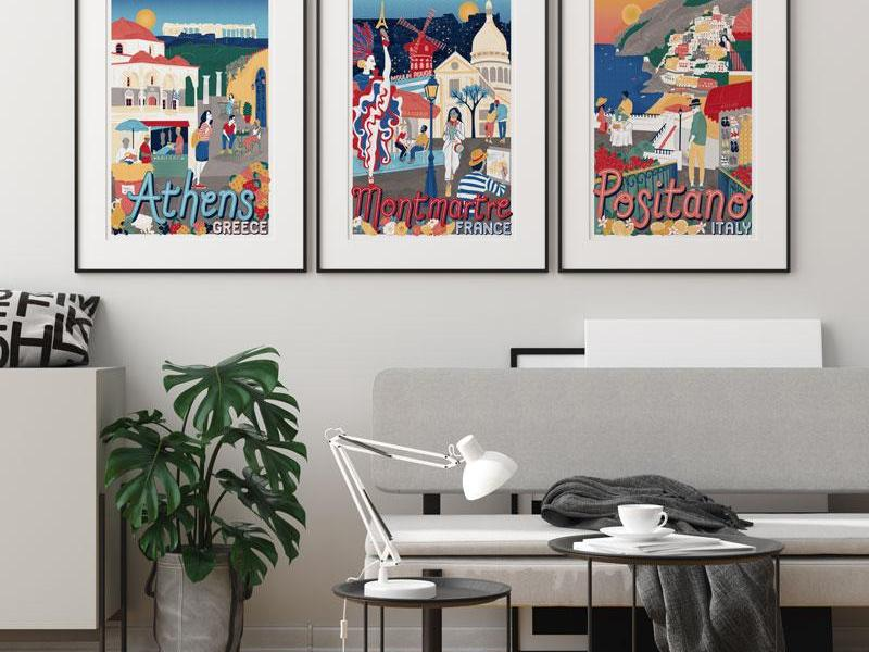 Three colourful illustrations of Athens, Montmartre and Positano hang on the wall of an office