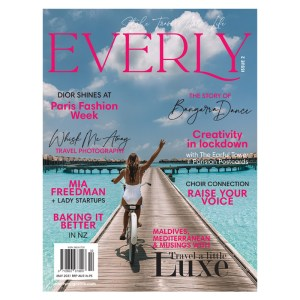 Everly magazine Issue 2 front cover shows a woman riding a bicycle along a wooden boardwalk surrounded by crystal-clear ocean and bungalows in the distance
