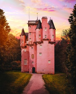 A pink painted castle stands at the end of a long driveway surrounded by forest and a pastel sunset sky