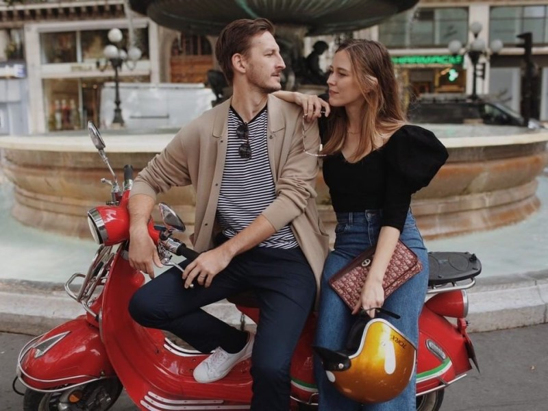 A man and woman sit on a red scooter looking at each other