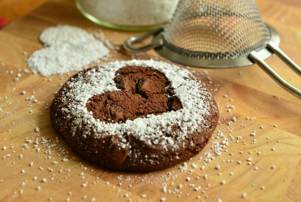 A chocolate biscuit featuring a heart shape made by icing-sugar sits on a kitchen table