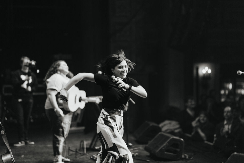 Black and white photo of two women standing on stage, one is holding a microphone and the other a guitar