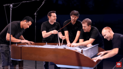 Image: 5 musicians playing one piano