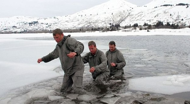 Image: Survival Training Navy Seals. 3 Men walking through a lake covered in ice, in the background, snow covered mountains.